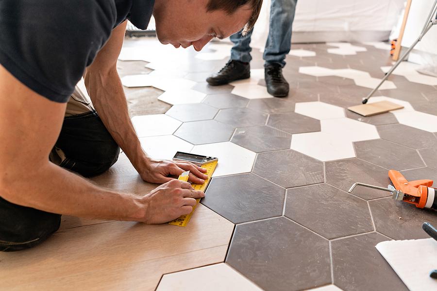 male worker installing new wooden laminate flooring.
